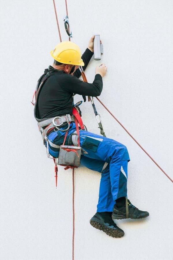 Ο επαγγελματικός εργαζόμενος επισκευάζει ένα φως στο κτήριο στοκ εικόνα