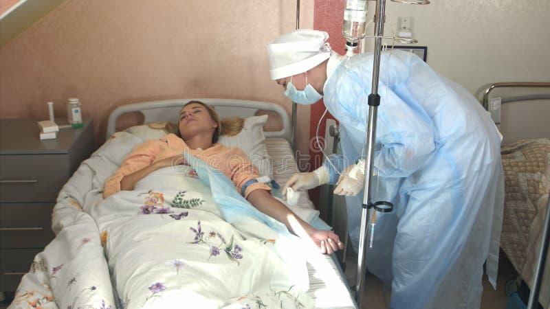 Ο επιδέξιος ιατρός παθολόγος βάζει dropper στο νοσοκομείο Το νέο anesthesiologist γιατρών γυναικών υποβάλλει dropper στοκ φωτογραφίες με δικαίωμα ελεύθερης χρήσης