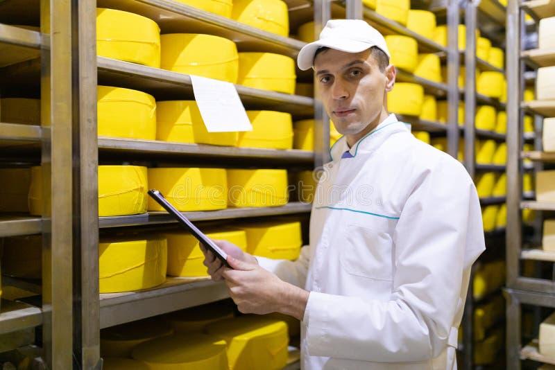 Ο επιθεωρητής κάνει τις σημειώσεις στο φύλλο στην αποθήκη εμπορευμάτων τυριών στοκ εικόνα με δικαίωμα ελεύθερης χρήσης