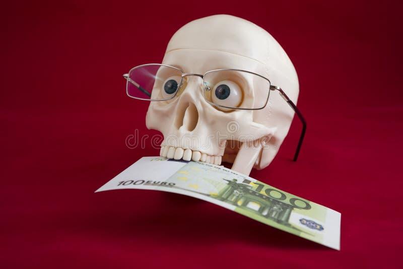 Ο επικεφαλής ενός ατόμου με τα γυαλιά, κρατά εκατό ευρώ στα δόντια του στοκ φωτογραφίες με δικαίωμα ελεύθερης χρήσης