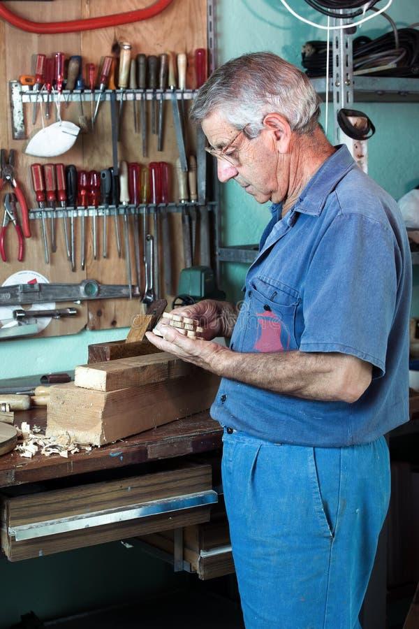 Ο επιπλοποιός εργασίας που κοιτάζει τα ξύλινα κομμάτια που τελείωσαν μέσα στοκ εικόνες
