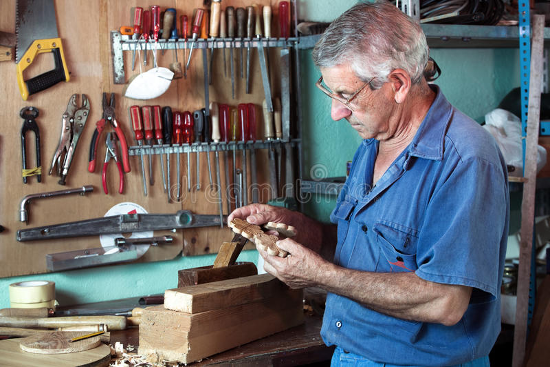 Ο επιπλοποιός εργασίας που κοιτάζει τα ξύλινα κομμάτια στο γκαράζ στοκ φωτογραφίες με δικαίωμα ελεύθερης χρήσης