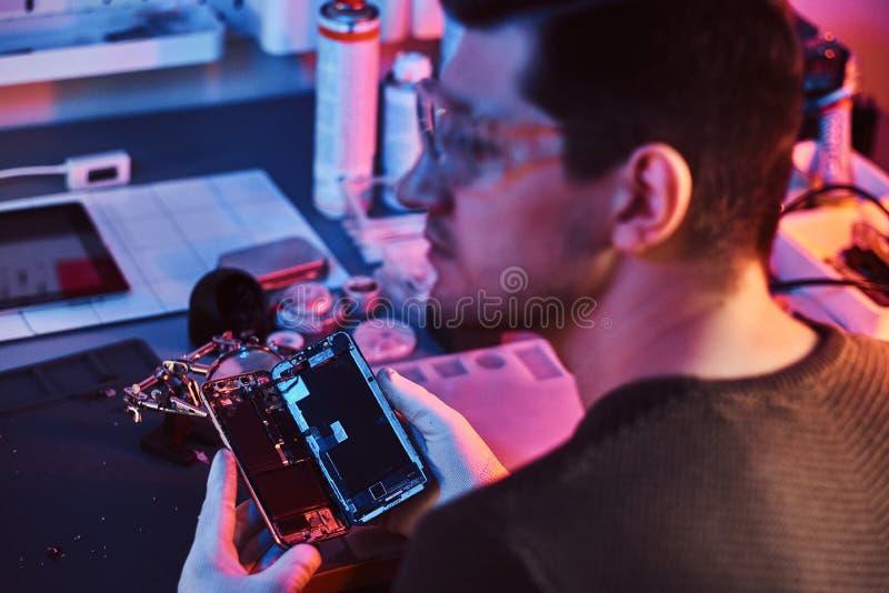 Ο επισκευαστής στα προστατευτικά δίοπτρα που κρατά ένα χαλασμένο smartphone, που κοιτάζει λοξά σε ένα σύγχρονο κατάστημα επισκευή στοκ εικόνα