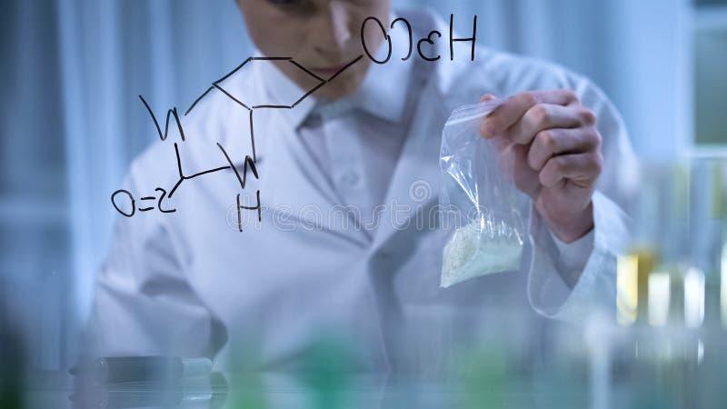 Ο επιστήμονας κρατά το δείγμα των λιπασμάτων που εφευρίσκονται από το χημικό τύπο του, έρευνα στοκ φωτογραφία