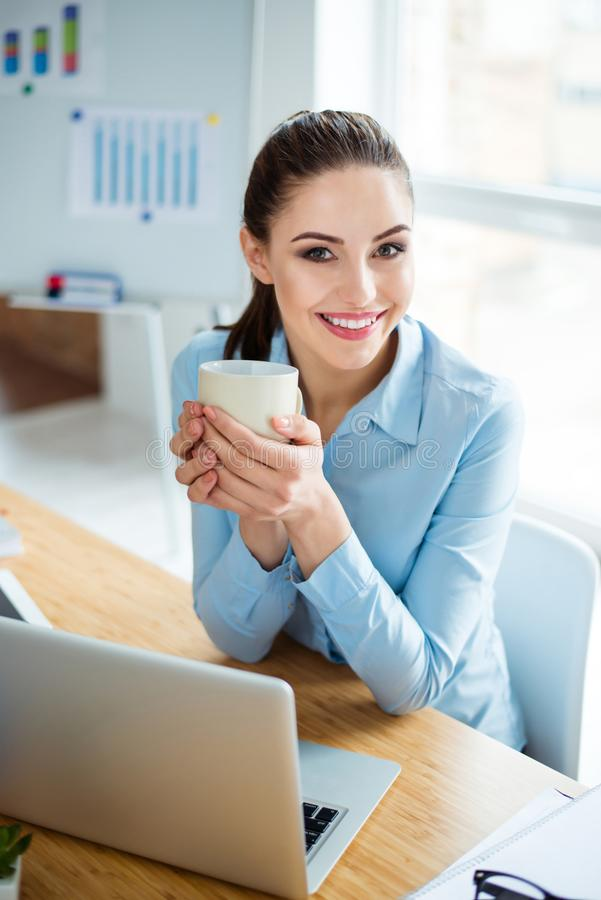 Ο επιτυχής εύθυμος γυναικείος οικονομολόγος στηρίζεται στο χώρο εργασίας της στοκ εικόνα
