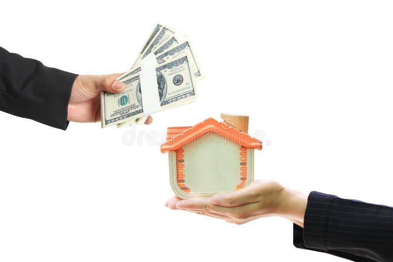 Ο επιχειρηματίας έδωσε τα χρήματα στη επιχειρηματία που κρατά το ξύλινο σπίτι στο άσπρο υπόβαθρο, τις ακίνητες εμπορικές συναλλαγ στοκ φωτογραφίες με δικαίωμα ελεύθερης χρήσης