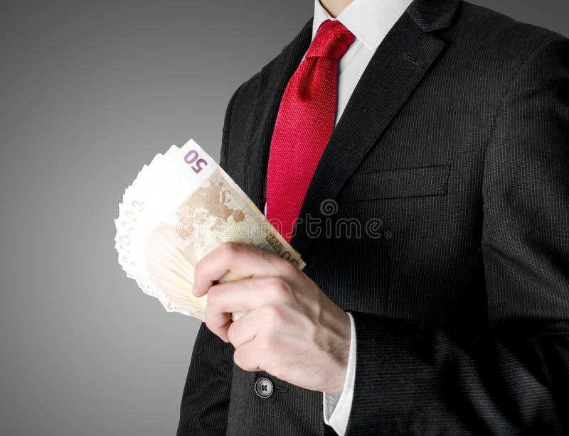 Ο επιχειρηματίας έντυσε στα χρήματα εκμετάλλευσης κοστουμιών στοκ φωτογραφία