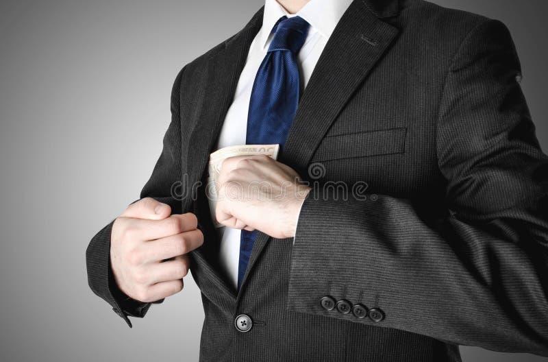 Ο επιχειρηματίας έντυσε στο κοστούμι βάζοντας τα χρήματα στην τσέπη του στοκ φωτογραφία με δικαίωμα ελεύθερης χρήσης