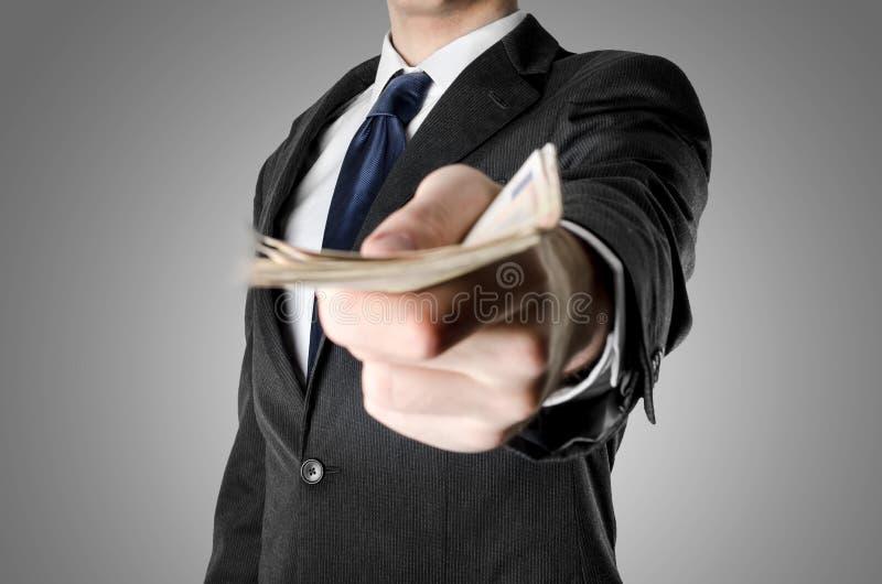 Ο επιχειρηματίας έντυσε στο κοστούμι που προσφέρει τα χρήματα στοκ φωτογραφίες