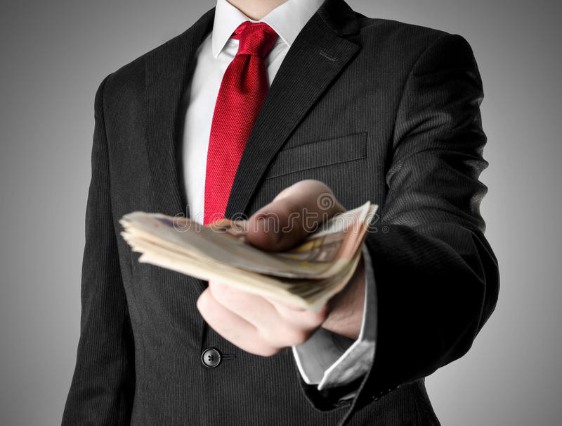 Ο επιχειρηματίας έντυσε στο κοστούμι που προσφέρει τα χρήματα στοκ εικόνες