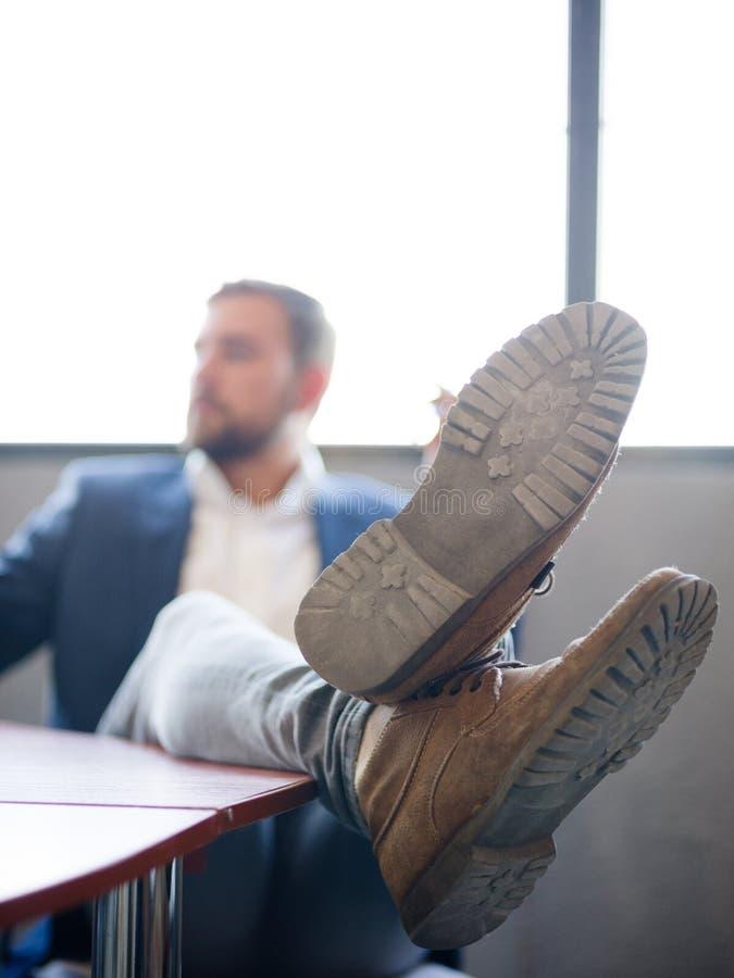 Ο επιχειρηματίας έριξε τα πόδια του στο γραφείο για να χαλαρώσει στοκ εικόνες