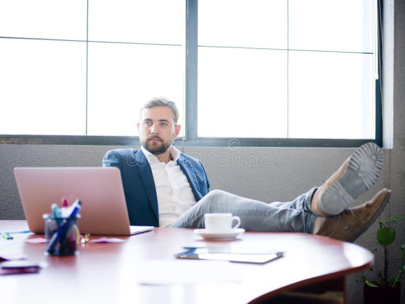 Ο επιχειρηματίας έριξε τα πόδια του στο γραφείο για να χαλαρώσει στοκ εικόνα με δικαίωμα ελεύθερης χρήσης