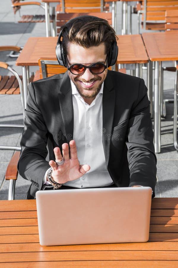 Ο επιχειρηματίας ή ο εργαζόμενος αρσενικών στο μαύρα κοστούμι και τα ακουστικά έχει τη συνομιλία στον υπολογιστή στοκ εικόνες με δικαίωμα ελεύθερης χρήσης
