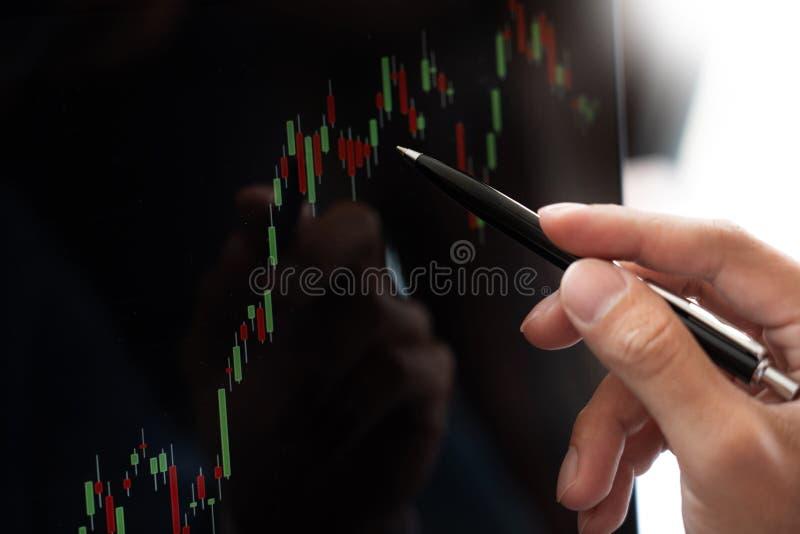 Ο επιχειρηματίας ή ο μεσίτης που εξετάζει το lap-top υπολογιστών που αναλύει για το χρηματιστήριο επενδύει τη γραμμή κεριών ανάλυ στοκ φωτογραφία