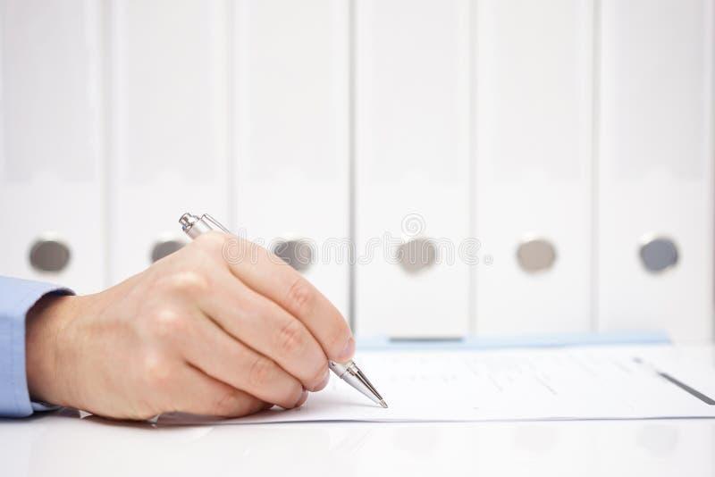 Ο επιχειρηματίας ή ο λογιστής υπογράφει το έγγραφο με τους συνδέσμους στο BA στοκ εικόνες