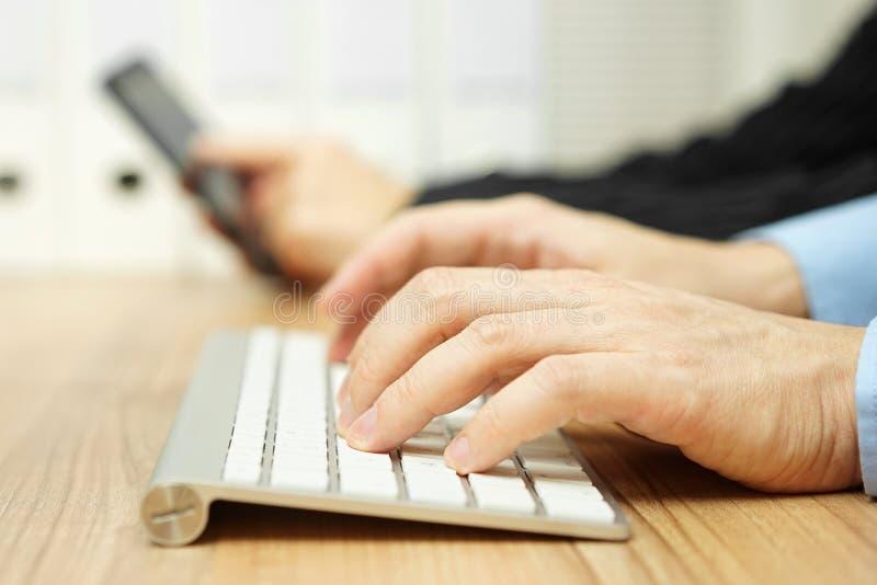 Ο επιχειρηματίας δακτυλογραφεί στο πληκτρολόγιο υπολογιστών για να έρθει σε επαφή με τους πελάτες W στοκ φωτογραφίες