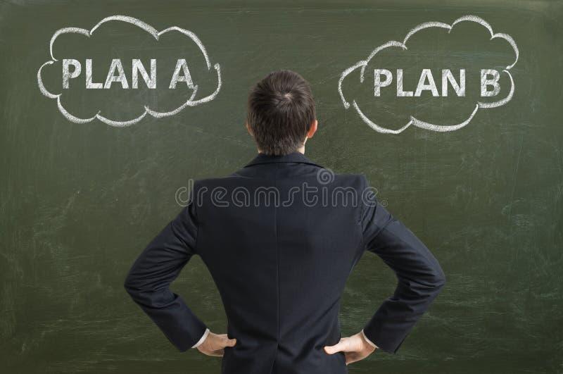 Ο επιχειρηματίας λαμβάνει την απόφαση και επιλέγει την καλύτερη επιχειρησιακή στρατηγική στοκ φωτογραφία