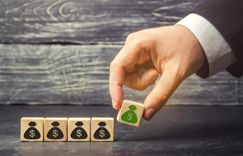 Ο επιχειρηματίας βάζει έναν φραγμό με μια εικόνα των δολαρίων Η κύρια συσσώρευση και η επιτυχής επιχείρηση Αυξανόμενοι προϋπολογι στοκ φωτογραφία με δικαίωμα ελεύθερης χρήσης