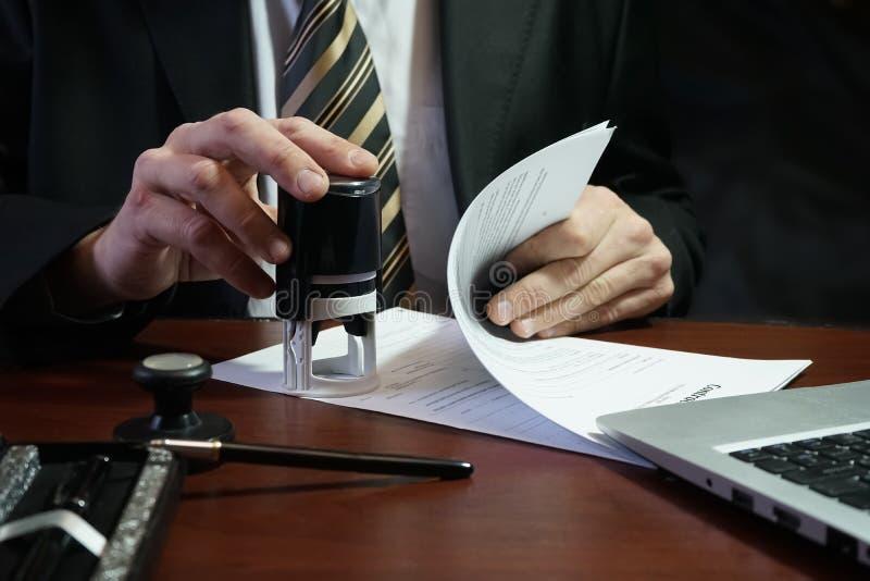 Ο επιχειρηματίας βάζει ένα γραμματόσημο στη σύμβαση στοκ εικόνα