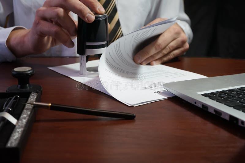 Ο επιχειρηματίας βάζει ένα γραμματόσημο στη σύμβαση στοκ εικόνες