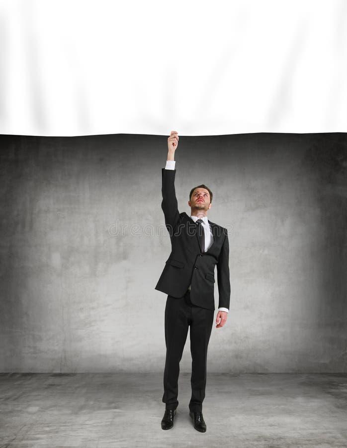 Ο επιχειρηματίας βάζει μια αφίσα στοκ φωτογραφία με δικαίωμα ελεύθερης χρήσης