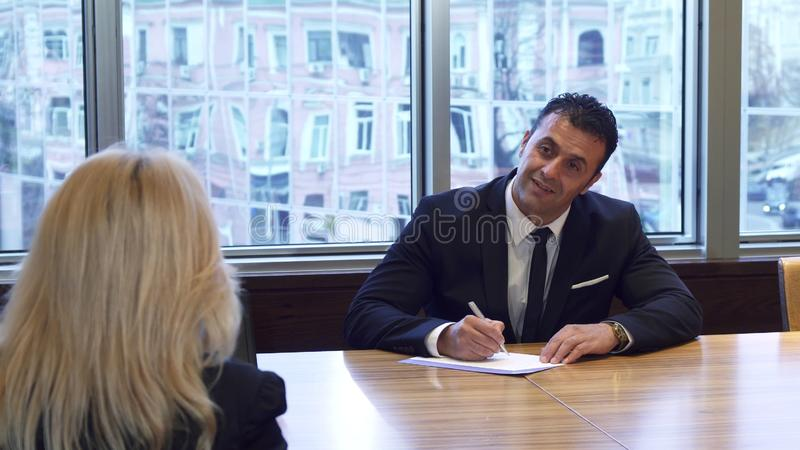 Ο επιχειρηματίας γράφει κάτι στα έγγραφά του στοκ φωτογραφία με δικαίωμα ελεύθερης χρήσης