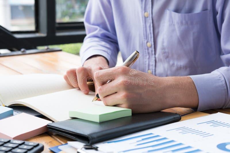 Ο επιχειρηματίας γράφει τη σημείωση για το σημειωματάριο στο γραφείο γραφείων το άτομο γράφει mem στοκ εικόνες