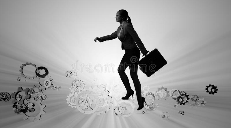 Ο επιχειρηματίας γυναικών που αναρριχείται cogwheels στοκ φωτογραφίες