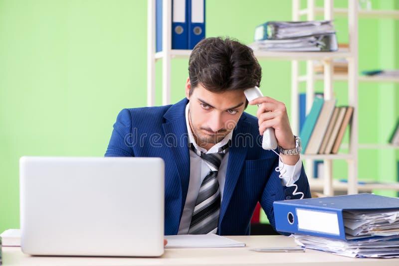 Ο επιχειρηματίας δυστυχισμένος με την υπερβολική συνεδρίαση εργασίας στο γραφείο στοκ εικόνες με δικαίωμα ελεύθερης χρήσης