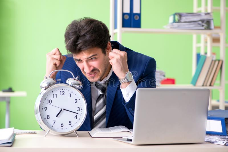 Ο επιχειρηματίας δυστυχισμένος με την υπερβολική συνεδρίαση εργασίας στο γραφείο στοκ εικόνα