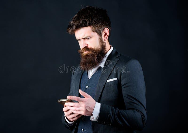Ο επιχειρηματίας εκαλλώπισε καλά το smartphone λαβής ατόμων Κοινωνικά δίκτυα smartphone χρήσης κοστουμιών ατόμων επίσημα Τύπος πο στοκ εικόνα
