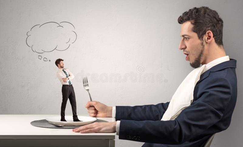 Ο επιχειρηματίας θέλει να φάει το μικρό άτομο στοκ εικόνες