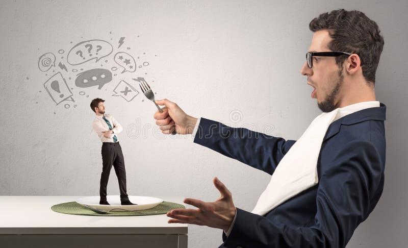 Ο επιχειρηματίας θέλει να φάει το μικρό άτομο στοκ εικόνα