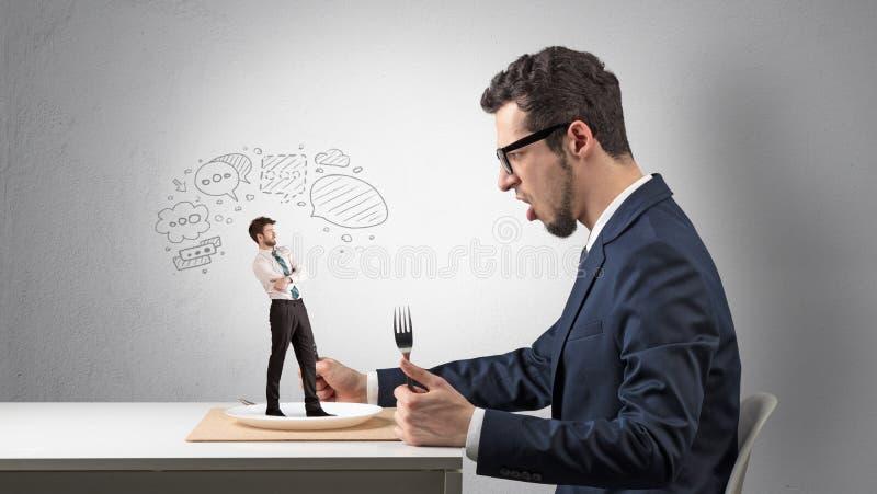 Ο επιχειρηματίας θέλει να φάει το μικρό άτομο στοκ φωτογραφίες με δικαίωμα ελεύθερης χρήσης