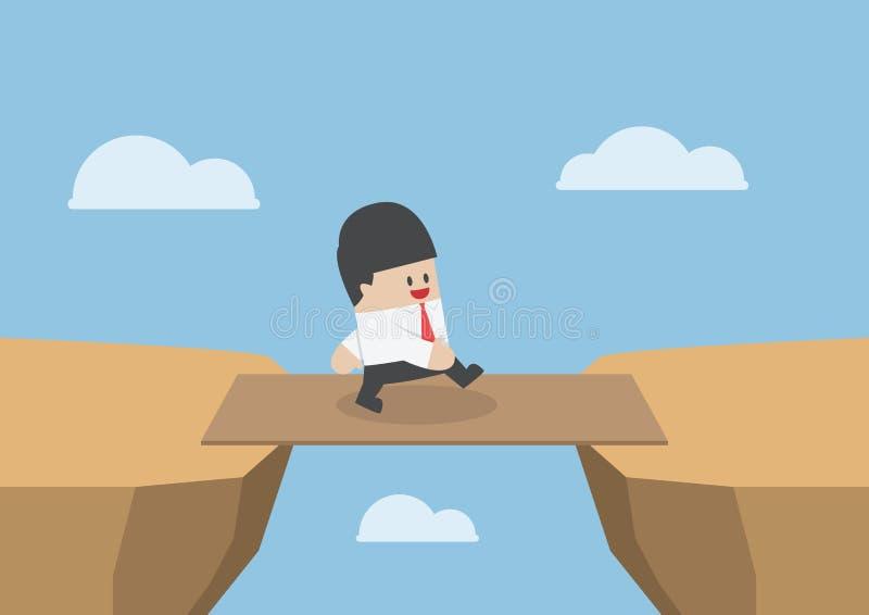 Ο επιχειρηματίας διασχίζει το χάσμα απότομων βράχων από τον ξύλινο πίνακα ως γέφυρα ελεύθερη απεικόνιση δικαιώματος