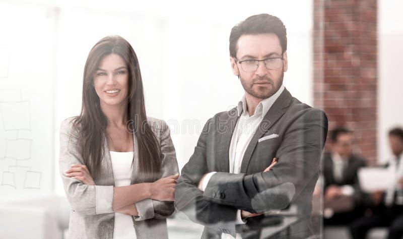 Ο επιχειρηματίας και η επιχειρηματίας κοιτάζουν μέσω του παραθύρου ενός σύγχρονου γραφείου στοκ εικόνα