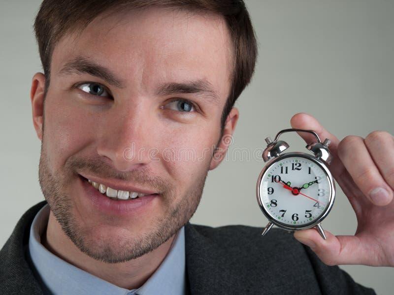Ο επιχειρηματίας κρατά ένα ξυπνητήρι στοκ εικόνα με δικαίωμα ελεύθερης χρήσης