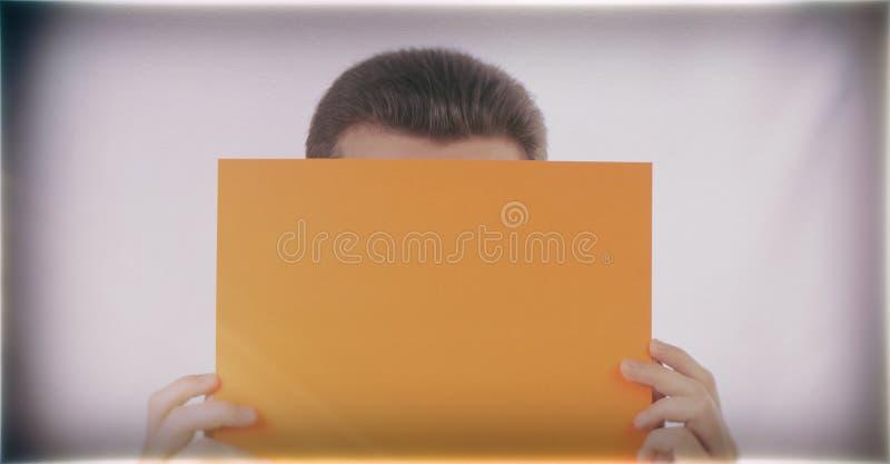 Ο επιχειρηματίας κρατά ένα πορτοκαλί φύλλο του εγγράφου στοκ εικόνα με δικαίωμα ελεύθερης χρήσης