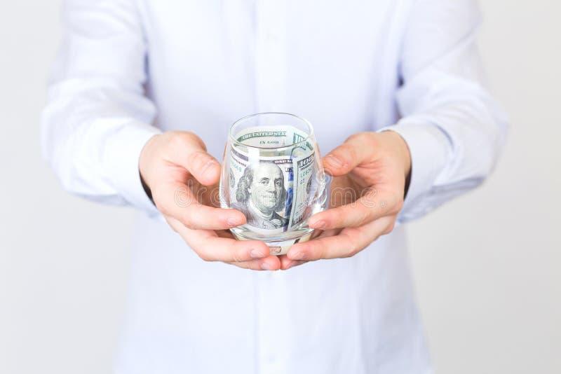Ο επιχειρηματίας κρατά το γυαλί με τα μετρητά στοκ φωτογραφία με δικαίωμα ελεύθερης χρήσης
