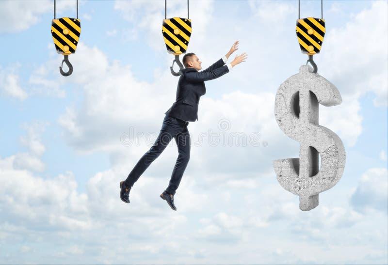 Ο επιχειρηματίας κρεμά στο γάντζο και φθάνει για το μεγάλο σημάδι δολαρίων στοκ φωτογραφίες