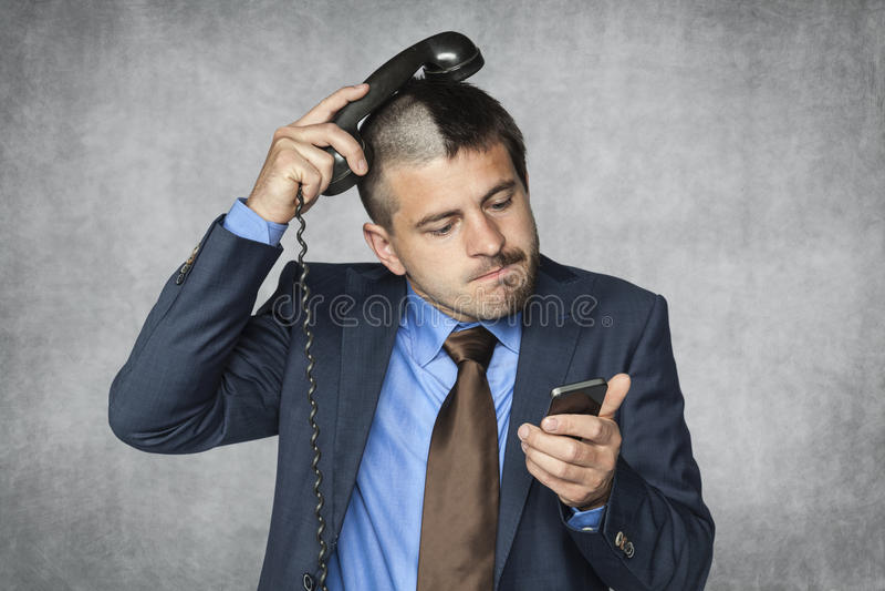 Ο επιχειρηματίας με ένα αστείο κούρεμα δεν μπορεί να χειριστεί το τηλέφωνο στοκ φωτογραφίες με δικαίωμα ελεύθερης χρήσης