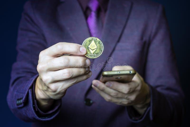 Ο επιχειρηματίας με μοβ στολή κρατά το χρυσό νόμισμα του αιθέρα ανάμεσα στα δάκτυλα, το έξυπνο σήμα κρυπτογραφίας στοκ φωτογραφία