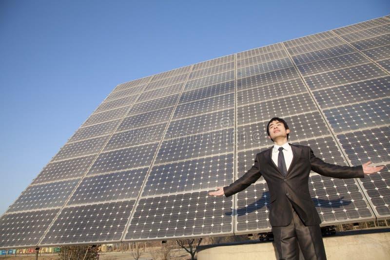 Ο επιχειρηματίας με τα όπλα μπροστά από τα ηλιακά πλαίσια στοκ εικόνες