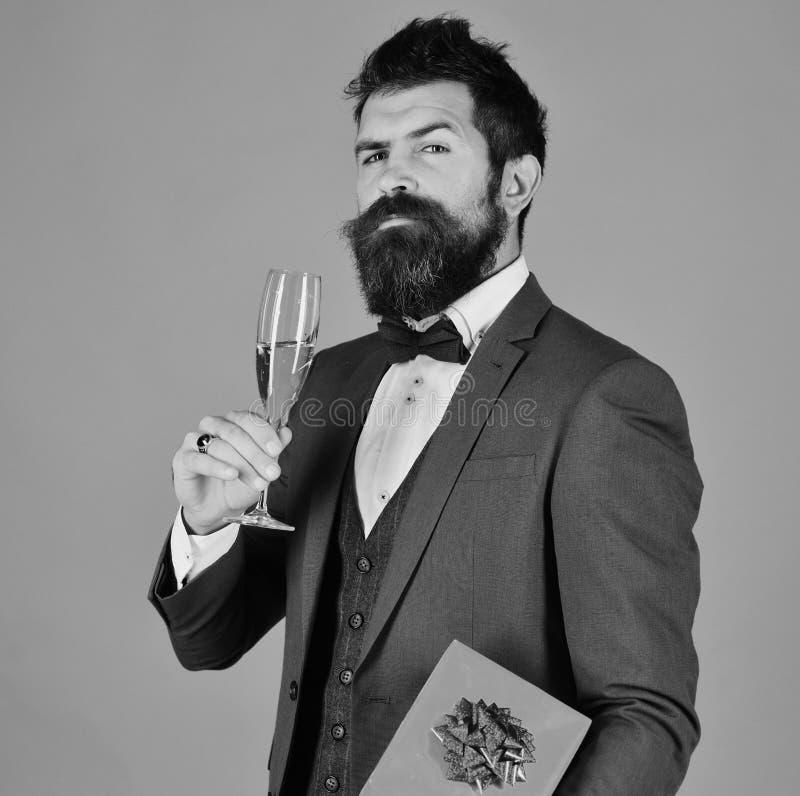 Ο επιχειρηματίας με το υπερήφανο πρόσωπο κρατά το λαμπιρίζοντας κρασί και το παρόν κιβώτιο στοκ εικόνα με δικαίωμα ελεύθερης χρήσης