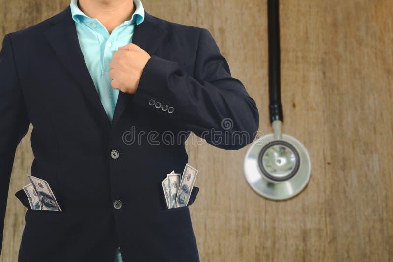 Ο επιχειρηματίας παρουσιάζει με το τραπεζογραμμάτιο στην τσέπη και το εργαλείο υγείας στοκ φωτογραφίες