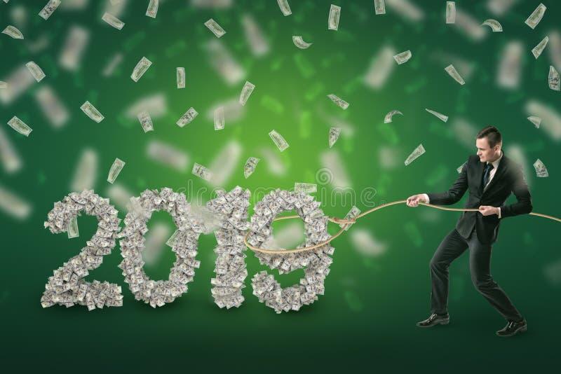 """Ο επιχειρηματίας πιάνει το σημάδι δολαρίων του """"2019 """"με το λάσο σχοινιών και τα χρήματα στον αέρα στο πράσινο υπόβαθρο απεικόνιση αποθεμάτων"""