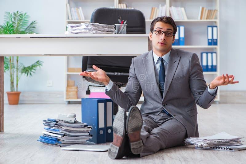 Ο επιχειρηματίας που εργάζεται και που κάθεται στο πάτωμα στην αρχή στοκ εικόνα