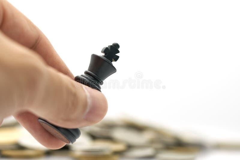 Ο επιχειρηματίας που κρατά ένα σκάκι βασιλιάδων τοποθετείται σε έναν σωρό των νομισμάτων χρησιμοποίηση ως επιχειρησιακή έννοια υπ στοκ εικόνα με δικαίωμα ελεύθερης χρήσης