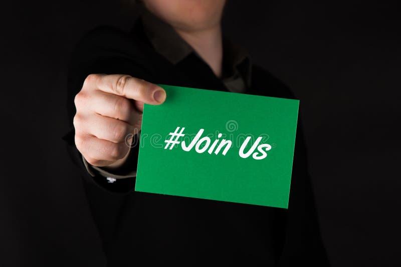 Ο επιχειρηματίας που κρατά την πράσινη κάρτα με το κείμενο hashtag μας ενώνει στοκ φωτογραφίες