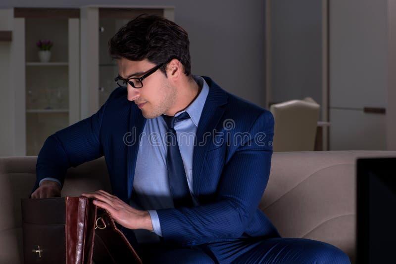 Ο επιχειρηματίας που προσέχει τη TV τη νύχτα αργά στοκ εικόνα